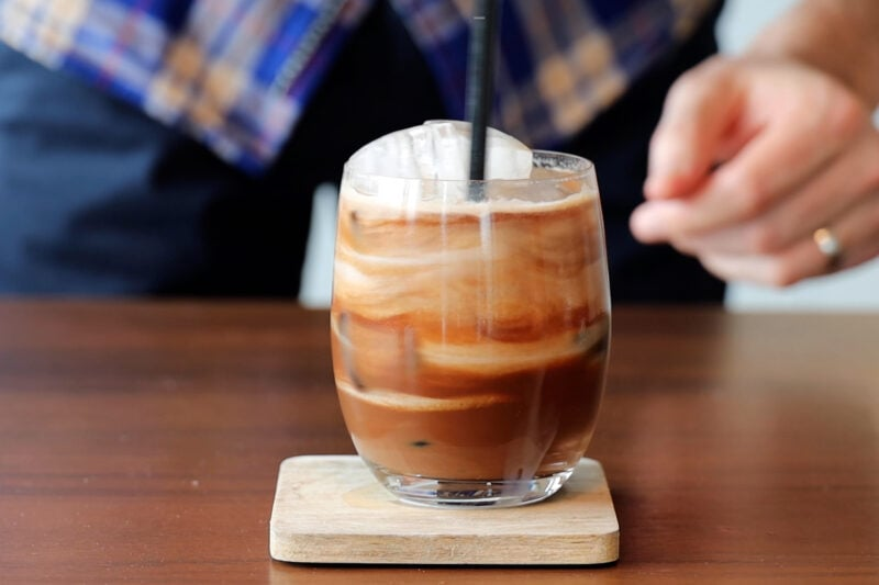 Mixing the iced coffee with the milk.